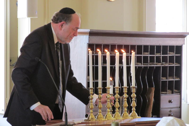 Rabbi Barry Marks, of Temple Israel in Springfield, lights the last of six memorial candles honoring victims and survivors of the Holocaust at a ceremony on April 12.
