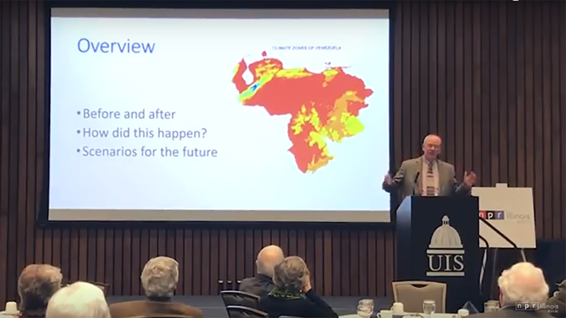 Michael Coppedge discusses the state of Venezuela on stage in front of projected slides.