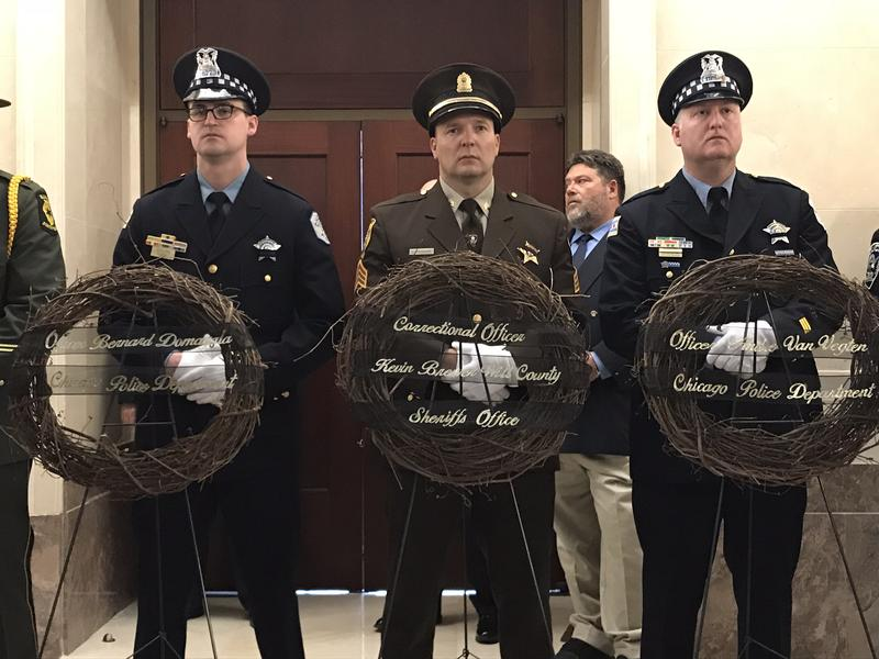 A color guard of Illinois police officers watches over four of six wreathes memorializing officers killed in the line of duty at a service on May 3.