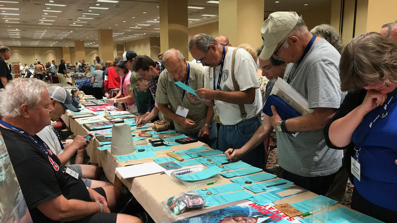 Collectors bid on items at a silent auction at the American Political Items Collectors conference in Springfield.