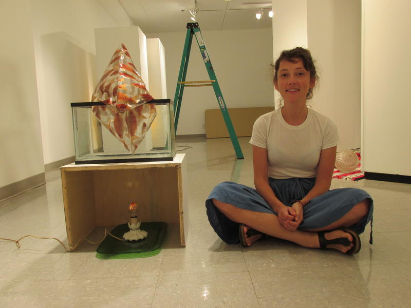 Allyson Packer sits by part of the exhibit as she continues installation