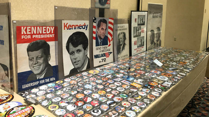 An exhibit table offers buttons and posters at the APIC conference in Springfield.