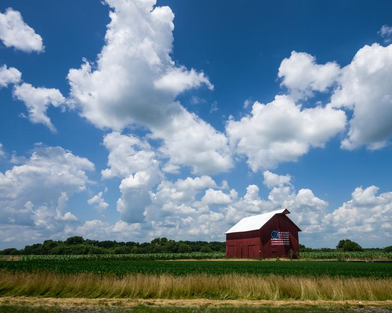 Barn with U.S. flag painted under big cloudy sky