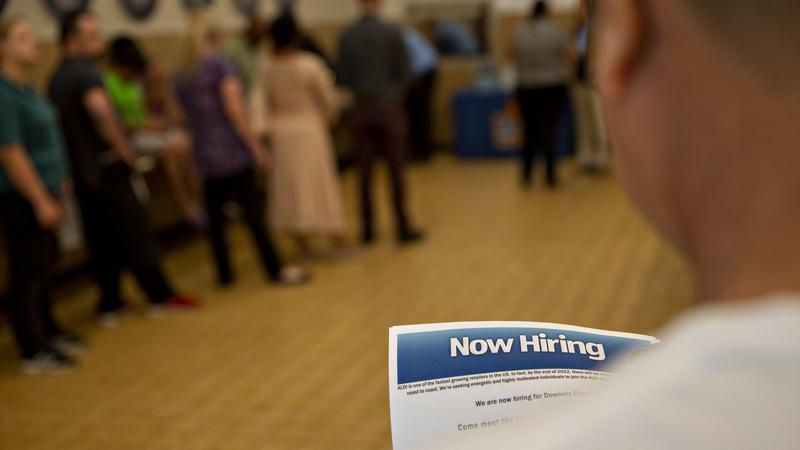 A job seeker holds an employment flyer during a hiring event at an Aldi Supermarket in Darien, IL in July.
