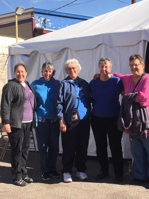 Dominican Sisters Anita Cleary (far left), and Sister Marcelline Koch (center), outside a food tent with friends Julie Wullner, Kathryn Raistrick (on Sister Marcelline's right) and fellow volunteer Sister Betty Baker, CND (next to Sister Anita).