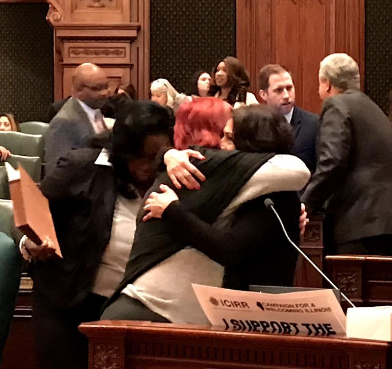 State Rep. Lisa Hernandez (D, left) receives a hug from Republican State Rep. Margo McDermed after the Illinois House votes to override Gov. Rauner's veto on the Voices Act on Nov. 28.