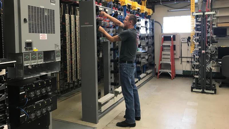 A technichian with Shawnee Communications in Lovington, Illinois, surveys the company's fiber internet connection.