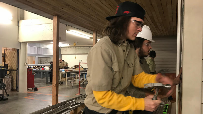 Shelby Landers and Matthew Mangold, both students at Capital Area Career Center, nail siding to the front of the house they're building in the trades class. Landers says he's happy to get out of the classroom and get more handson experience.