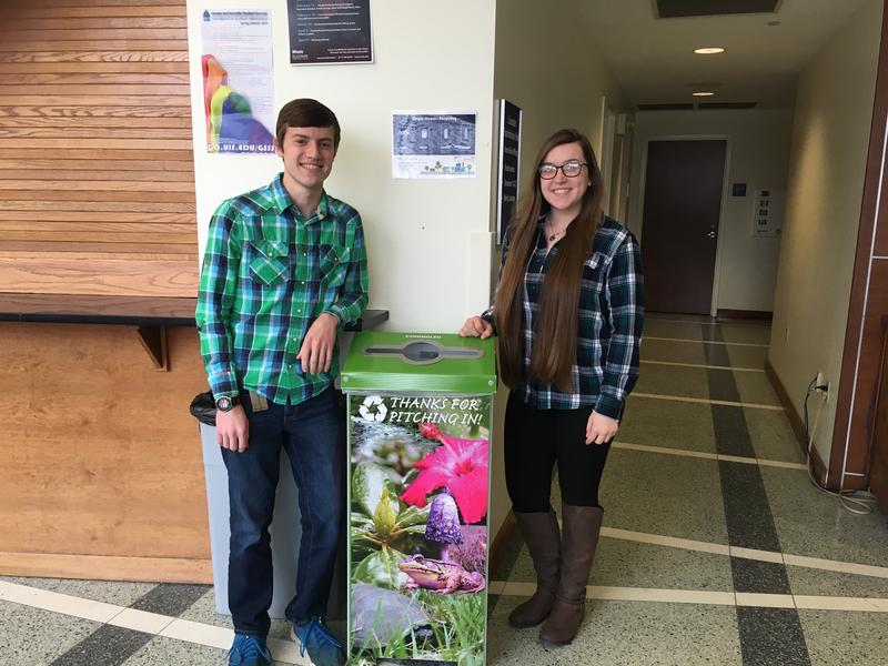 """From left, Caleb Froidcoeur and Marissa Jones stand next to their """"bedazzled"""" recycling bins, set up to test a hypothesis about recycling habits at UIS"""