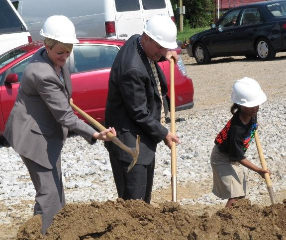 Principal Meribeth Gaines, Superintendent Stu Silberman, and a student turned over dirt at the elementary school construction site