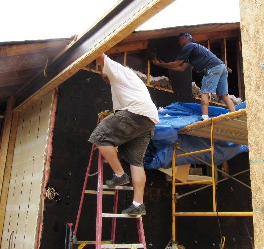 Timothy Gelenster (left) and Kenny Johnson work on a room addition at a Lexington home.