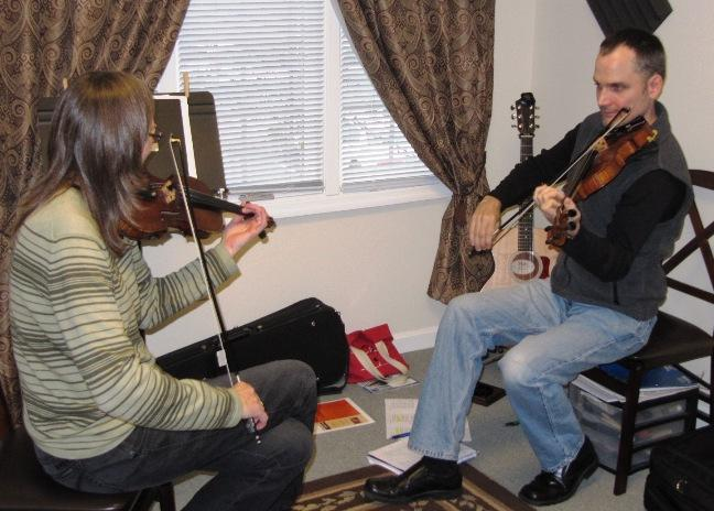 Daniel Carwile (right) is a master fiddler teaching Karen Jones in the artist apprenticeship program.