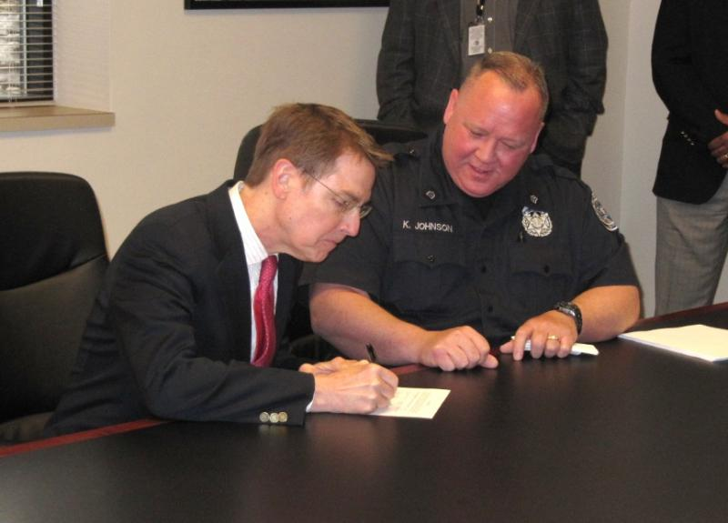 Mayor Jim Gray (left) signs the contract with Sgt. Kevin Johnson. Photo by Brenna Angel.