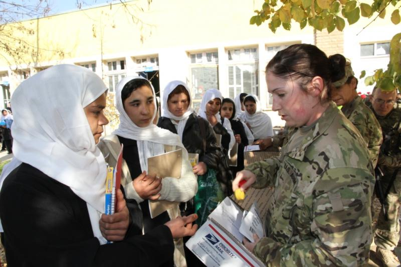 Kentucky Guardsman Sgt. Heather Carrier, Agi-business Development Team 3, passes out school supplies to Afghan students at a local school in Kapisa Province, Afghanistan. (photo by Kentucky National Guard Agribusiness Development Team 3)