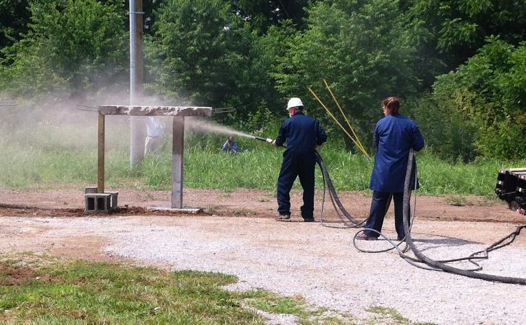 Researchers used a hose to spray a super fast setting concrete called Tekcrete on two wooden posts at the University of Kentucky Center for Applied Energy Research.