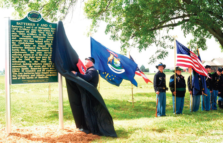 As a Michigan flag waves in the background, Richmond Battlefield Superintendent Phillip Seyfrit unveils a marker Saturday morning commemorating the service of Michigan soldiers in the 1862 Battle of Richmond.