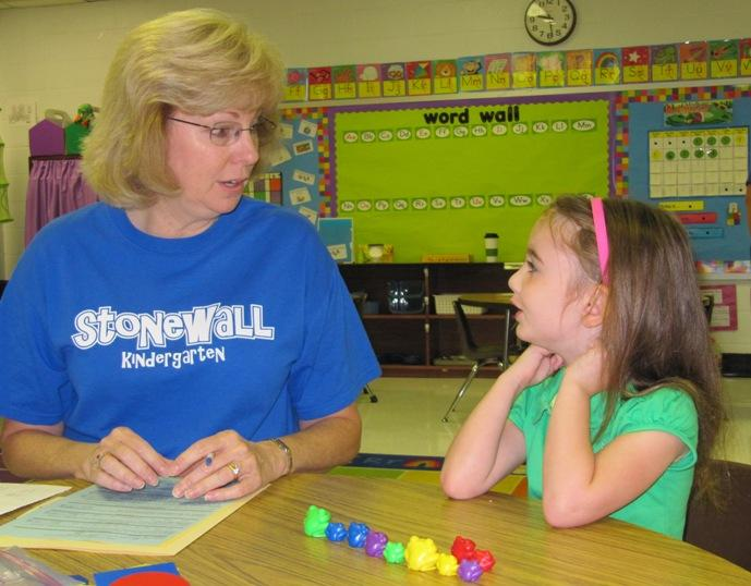 Teacher Becky Hall talks with Mallory Grimm about starting Kindergarten. - photo by Brenna Angel