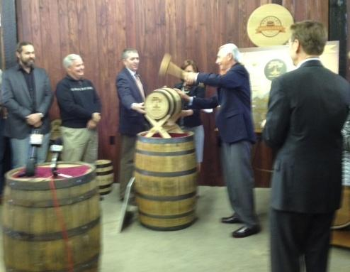 With Lexington Mayor Jim Gray looking on, Kentucky Governor Steve Beshear pops a bung into a ceremonial bourbon barrel signalling the addition of seven new Craft Distilleries to the Kentucky Bourbon Trail