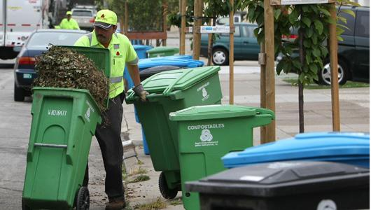 A worker in San Francisco collects compostable organic material separate from recycling and trash containers. - Getty Images