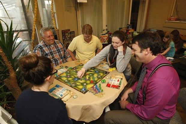 Convention Organizers Chris Grzywacz (back, left) and Greg Franseth (Far right) play a board game with the family.