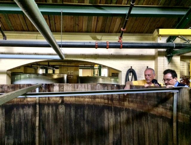Four Roses Master Distiller Jim Rutledge and WUKY's Alan Lytle peer over a giant vat in a behind the scenes tour