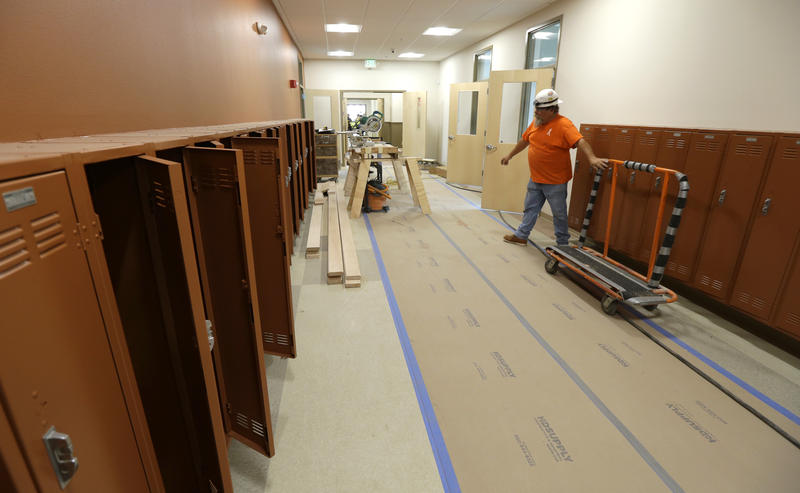 In this July 13, 2015 photo, Jerry Kellogg of Master Millwork wheels a lumber cart past open lockers in a hallway of the Destiny Charter Middle School in Tacoma, Wash.