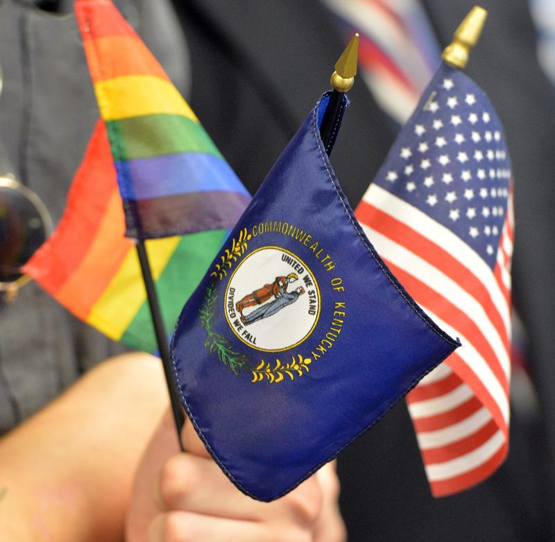 A person holds up the Flag of the Commonwealth ofKentucky, the United States Flag and the Rainbow Flag during a press conference discussing the Supreme Court decision to legalize same sex marriage Friday, June 26, 2015, in Louisville, Ky.