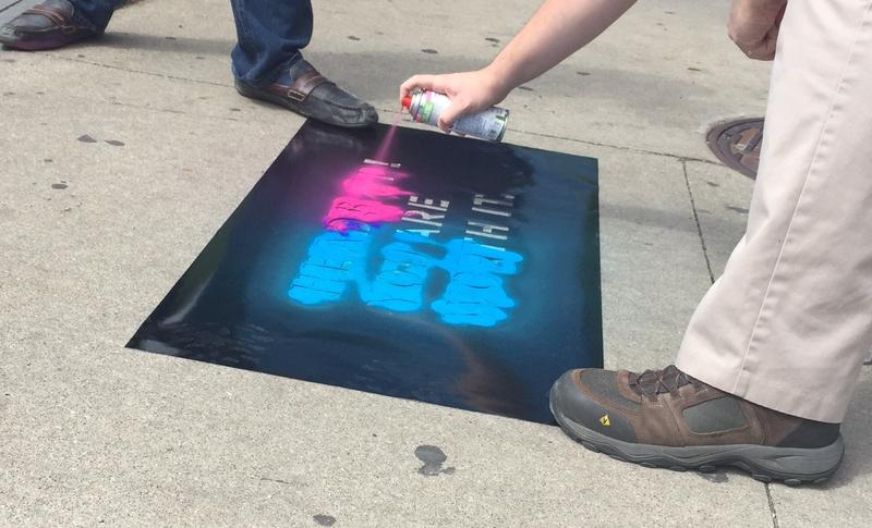 Safe Streets campaigner spray-paints a message for distracted pedestrians in downtown Lexington on June 8, 2017.