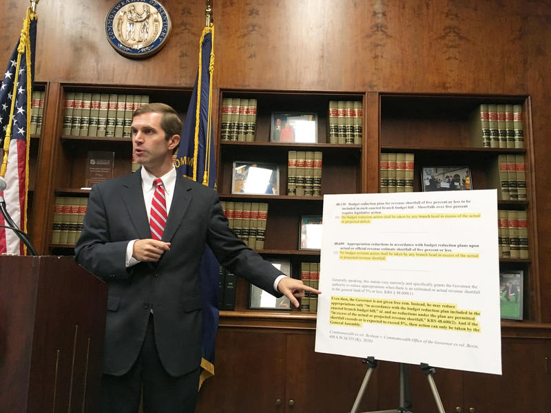 Kentucky Democratic Attorney General Andy Beshear points to state law he says prohibits the governor from implementing spending cuts that exceed a projected shortfall, in Frankfort, Ky., on Tuesday, Sept. 12, 2017.