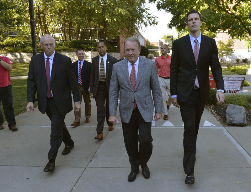University of Louisville interim President Greg Postel, center, walks with David Padgett, right, to a press conference where it was announced that Padgett will be Louisville's interim men's basketball coach Friday, Sept. 29, 2017, in Louisville, Ky.