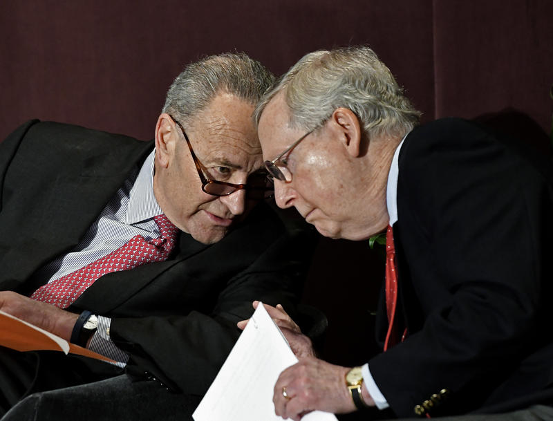 Senate Minority Leader Charles Schumer, D-N.Y., left, leans in to speak to Senate Majority Leader Mitch McConnell, R-Ky., before his speech at the McConnell Center's Distinguished Speaker Series Monday, Feb. 12, 2018, in Louisville, Ky.