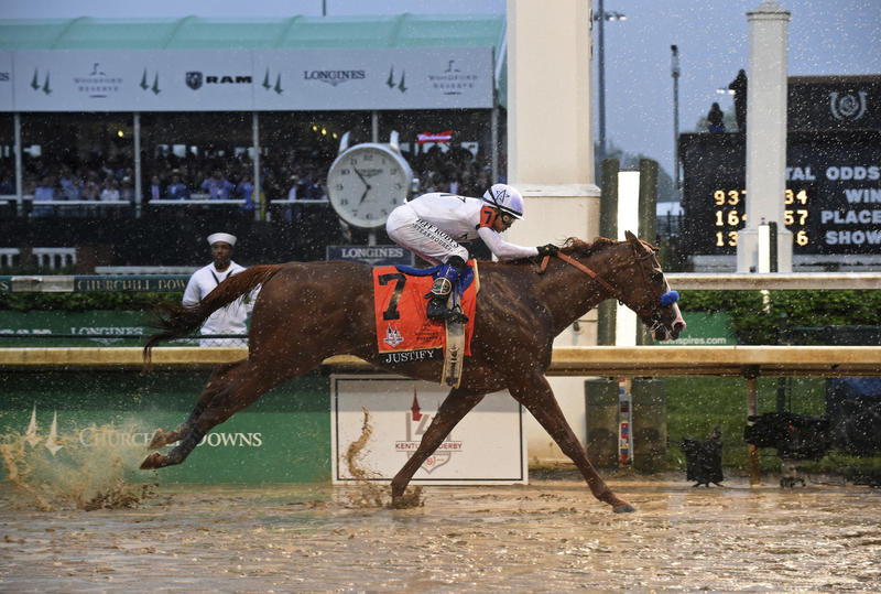 Justify, ridden by jockey Mike Smith, wins the 144th Kentucky Derby, the wettest in history, on Saturday, May 5, 2018, at Churchill Downs in Louisville, Ky.