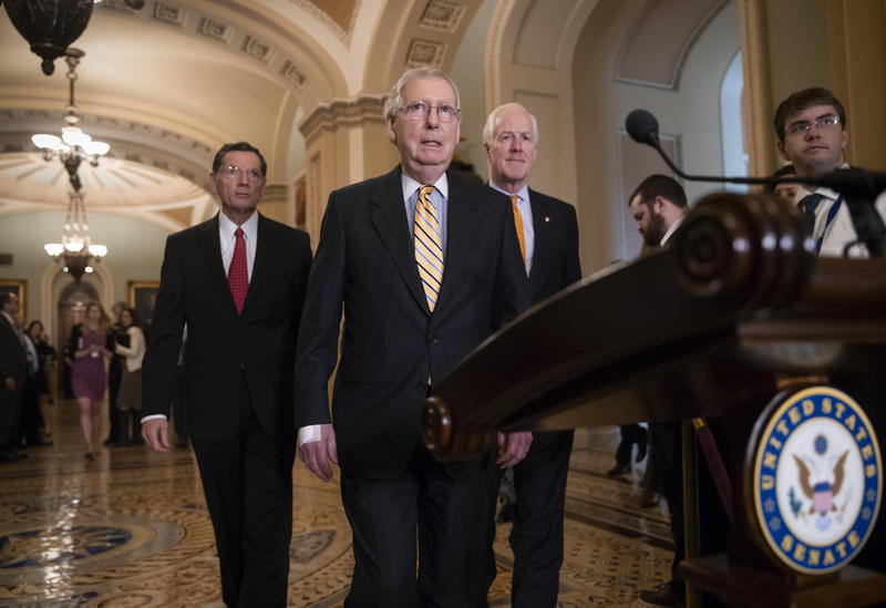 Senate Majority Leader Mitch McConnell, R-Ky., center, flanked by Sen. John Barrasso, R-Wyo., left, and Majority Whip John Cornyn, R-Texas, arrives to tell reporters he intends to cancel the traditional August recess.