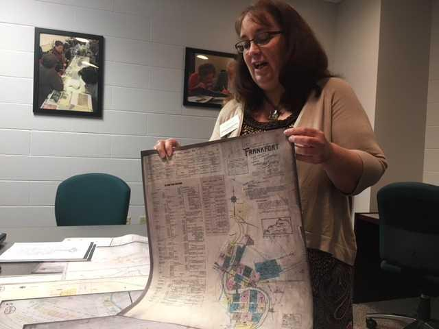Cheri Daniels, head of reference services holds up a historical map of distillery locations in Frankfort