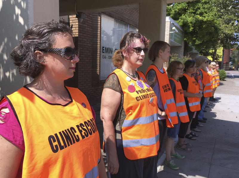 FILE - In this Monday, July 17, 2017 file photo, escort volunteers line up outside the EMW Women's Surgical Center in Louisville, Ky.