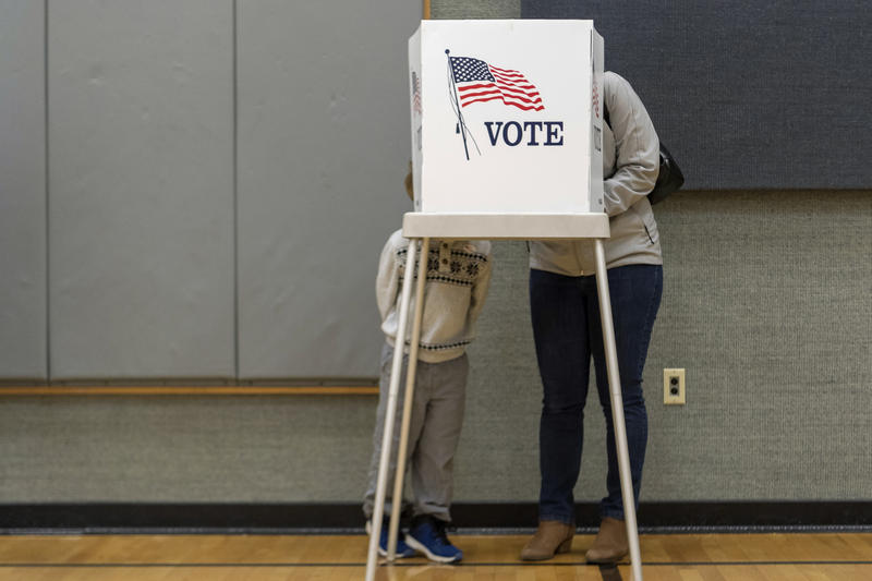 Democratic congressional candidate Amy McGrath stands stands in the voting booth with her son Theodore on Election Day in Georgetown, Ky., Tuesday, Nov. 6, 2018.