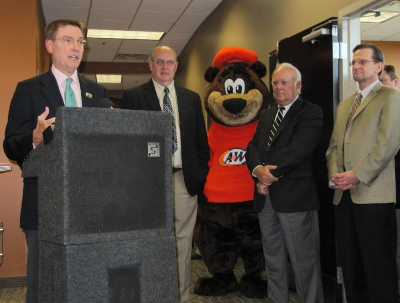 Lexington Mayor Jim Gray (left) with A & W executives (and Rooty the Great Root Bear) at the company's ribbon cutting.