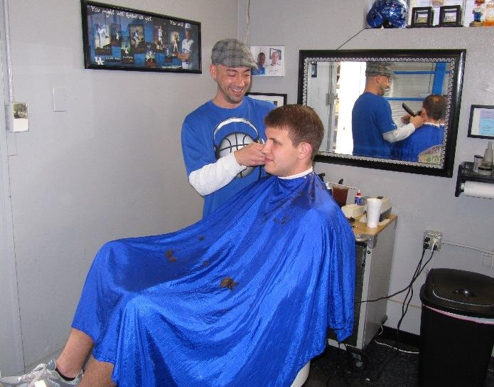 Ryan Lykins cuts Stuart Hines' hair at Wildcuts Barber Shop