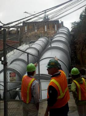 At this hydroelectric damn water passes through the penstocks, as Alcoa employees observe