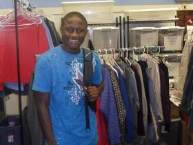 Abu, from Africa, smiles in the ''Giving Closet'' at the Newcomers School in Greensboro