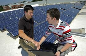 NCSU students study an array of solar panels on top of the NSF FREEDM Systems Center.