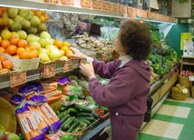 A shopper examines produce at Deep Roots grocery.