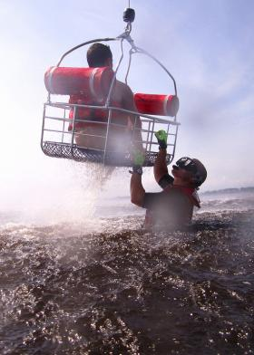 A rescue swimmer from Coast Guard Air Station Elizabeth City trains with rescue basket from a MH-60 Jayhawk helicopter.