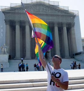 A man waves a flag in support of gay rights in front of the Supreme Court building.
