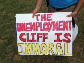 Man holds Unemployment Cliff Poster