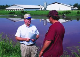 A USDA official meets with a hog farmer in Johnston County in 2011 to review animal waste management system.