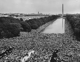 View of the crowd at 1963 Civil Rights March on Washington, D.C. A wide-angle view of marchers along the mall, showing the Reflecting Pool and the Washington Monument.