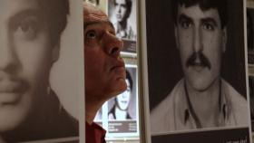 Photo: Assaad Chaftari walking through an exhibition of people who disappeared during the Lebanese Civil War.