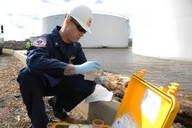 Photo: Michael Shannon, an U.S. Coast Guard marine science technician, takes a water sample near a damaged tank at an oil refinery in Sewaren, N.J., which leaked after Hurricane Sandy struck the region.