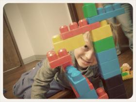 A child builds a lego tower in a doctor's waiting room.